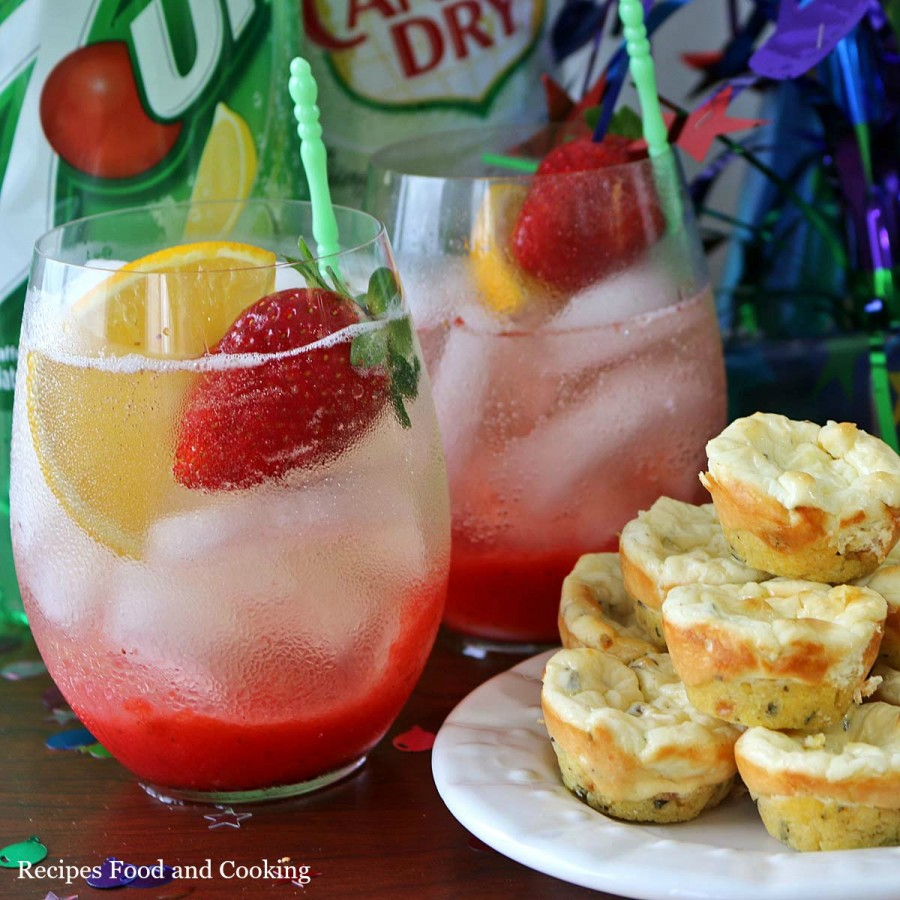 Side view of strawberry citrus drink mix with a strawberry and lemon slice with seven up and Canada Dry bottles.